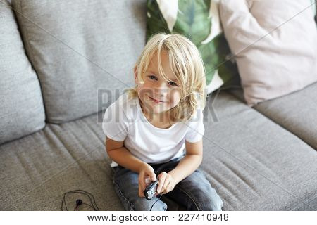 Cute Little European Boy With Long Blonde Hair Sitting On Comfortable Sofa In Living Room, Dressed I