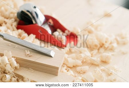 Handmade Woodwork: A Small Red Plane And Chisel On The Boards In Shavings. Close-up.
