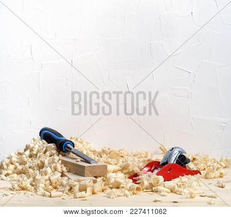 Handmade Woodwork: A Small Red Plane And Chisel On The Boards In Shavings