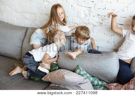 Action Shot Of Four Naughty Children Siblings Fooling Around At Home, Turning Living Room Upside Dow