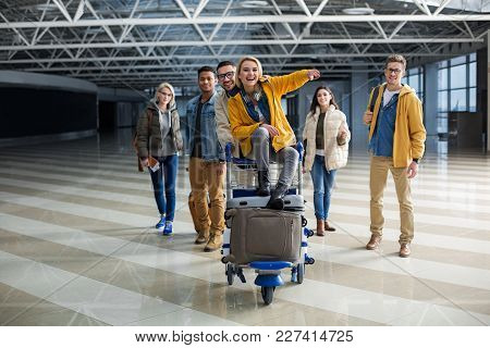 Content Company Of Young People Getting Ready For Travelling. They Are Carrying Cart With Baggage Th