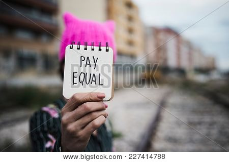 closeup of a young woman outdoors wearing a pink pussycat hat showing a piece of paper in front of her face with the text pay equal written in it