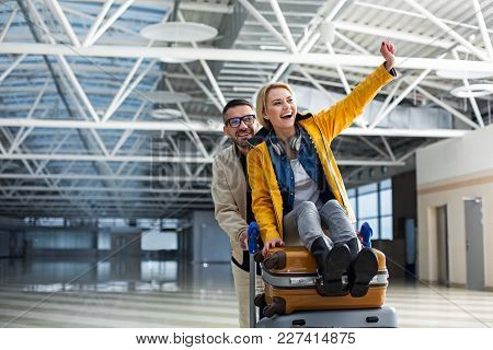 Young Glad Man Pushing Airport Trolley With Suitcases And Woman. She Is Sitting On It With One Hand