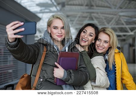 Waist Up Portrait Of Optimistic Girls Making Snapshot On The Phone While Standing At The Airport