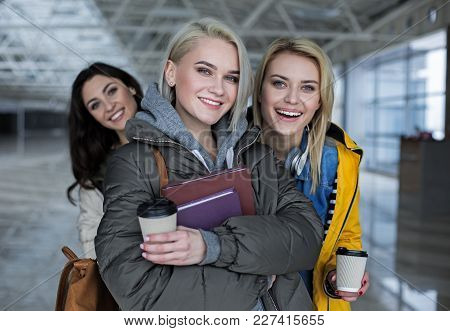 Portrait Of Three Happy Friends Standing In The Hall With Cups And Books. Focus On Two Blonde Haired