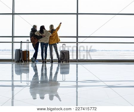 Girls Staring At Runway In The Terminal. They Are Standing With Their Backs And Hugging. Copy Space