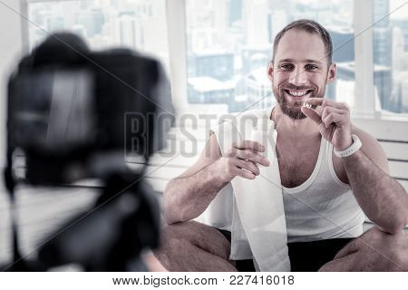 Help For Body. Jolly Vigorous Male Blogger Smiling While Demonstrating Vitamins And Recording Video
