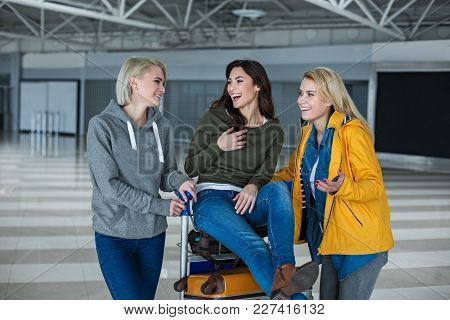 Three Adults Are Talking At The Airport And Laughing. One Of Them Is Resting On The Top Of Baggage T