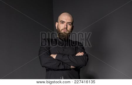 Handsome Bald Bearded Guy On A Black Background. The Man In The Black Shirt. A Bald Guy In A Shirt.