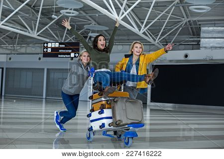 Back To The Childhood. Portrait Of Happy Women Having A Good Time At The Airport. They Are Rolling E