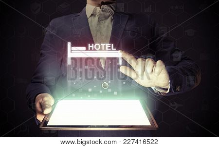 Image Of A Man With A Smartphone In His Hands. He Presses On The Hotel Icon. Search And Online Reser