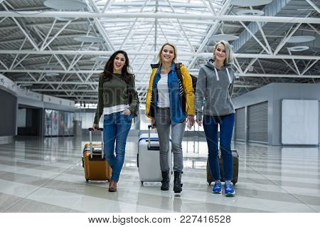 Full Length Portrait Of Glad Friends Taking A Trip On The Airplane. They Are Walking Through Airport