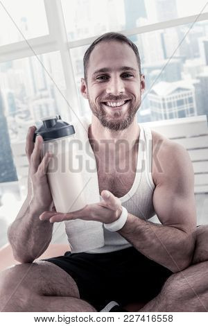 Convenient Format. Enthusiastic Handsome Merry Sportsman Showing Bottle While Posing On The Blurred