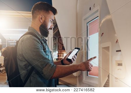 Summer Night. Young Hipster Man With Beard Stands On City Street And Touches Digital Display While L