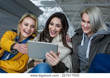 Technology Concept. Trio Of Ladies Having Fun With Gadget. They Are Staring At Device And Laughing
