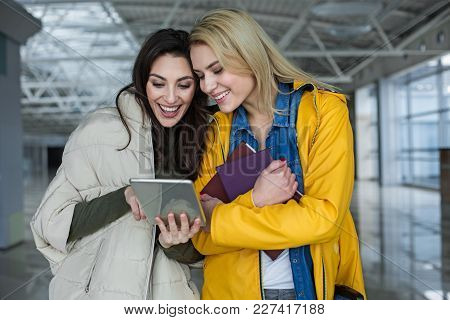 Attractive Women Laughing While Looking At Tablet. One Is Pointing At Device And Other Holding Books