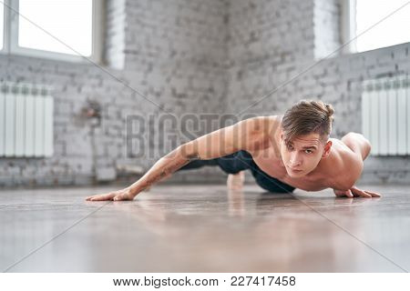 Athletic Young Man Doing Push Ups On The Floor. Young Man Workout In Fitness Club.