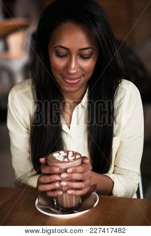 hot chocolate with marshmallows in hand of happy african woman
