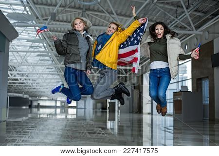 Overjoyed Females Triumphing Going On A Trip. Girls Are Leaping With American Banner And Bannerettes