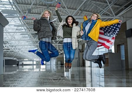 Dreams Come True. Content Girls Jumping For Joy With Flags Of United States. They Are Going Travelin