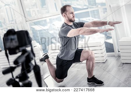 Simple Workout. Nice Confident Male Blogger Balancing While Working Out And Rising Hands