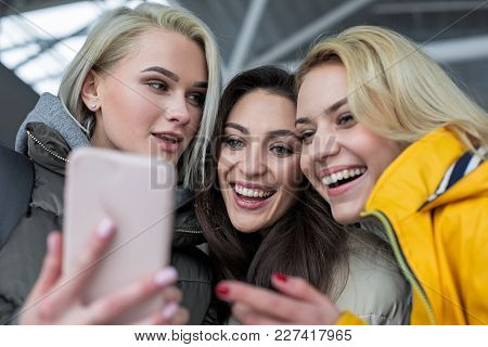 Technology Concept. Young Women Staring At Smartphone Expressing Satisfaction. Focus On Faces