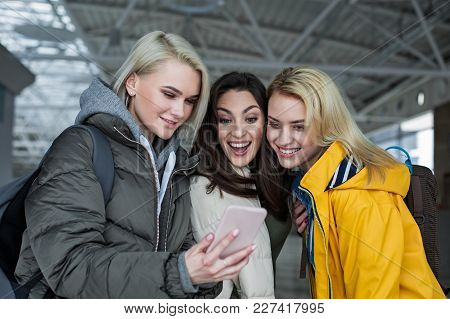 Female Company Standing In The Terminal And Looking At Mobile Screen With Delight