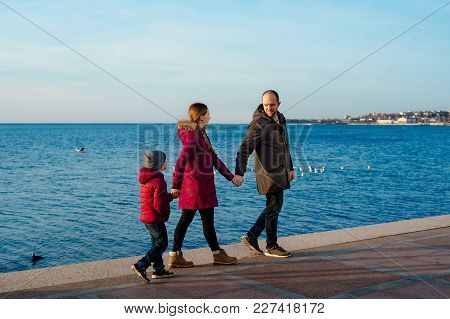 Happy Family Standing Near The Sea At The Day Time. Concept Of Friendly Family.