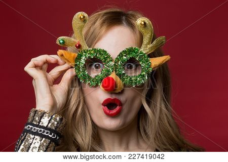 Portrait Of Eccentric Blonde Lady Holding Colorful Reindeer Mask And Looking At Camera In Amazement.