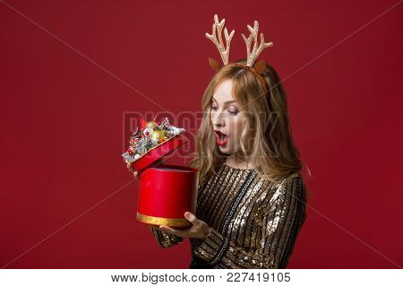 Surprised Attractive Woman In Reindeer Antlers Headband Opening Fancy Cylindrical Box. Isolated On R