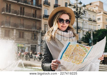 Young Smiling Woman Tourist In Hat And Sunglasses Stands On Street Of Ancient European City And Hold