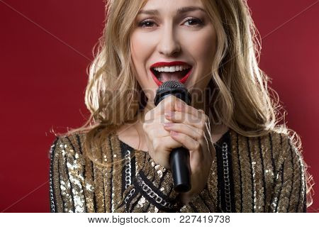 Beautiful Serene Lady Holding Speaker Close To Her Mouth And Performing A Song. Isolated On Red Back