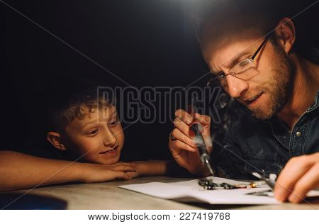 Father Soldering With Electric Soldering Iron And His Little Son Watches How He Works