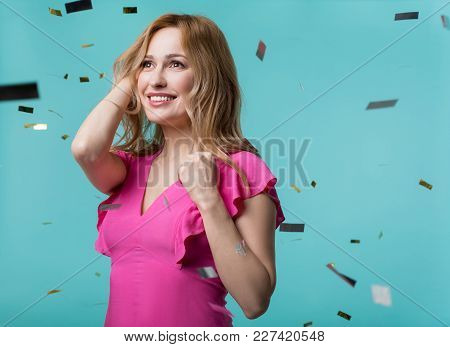 Portrait Of Glad Attractive Woman Standing Surrounded By Confetti And Looking Ahead With Happy Smile