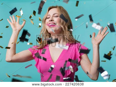 Portrait Of Joyful Female Standing In Cloud Of Confetti With Raised Hands And Closed Eyes. Isolated