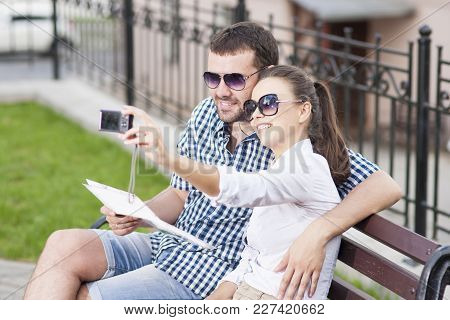 Traveling  Concepts. Young Caucasian Couple In Love Sitting On Bench Outdoors While Taking Selfie Pi
