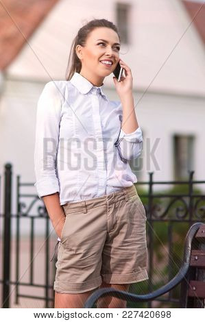 City Lifestyle Concepts. Pretty Smiling Caucasian Brunette Woman Speaking On Cellphone. Posing Outdo