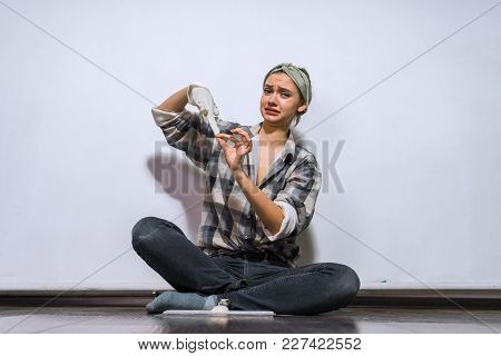 A Discontented Young Girl In A Shirt Sits On The Floor In Her Apartment, Removes Rubber Gloves