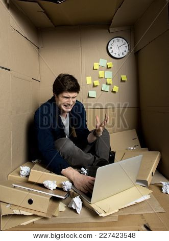 White Fury Concept. Full Length Of Young Annoyed Businessman Is Sitting Inside Small Cardboard Offic