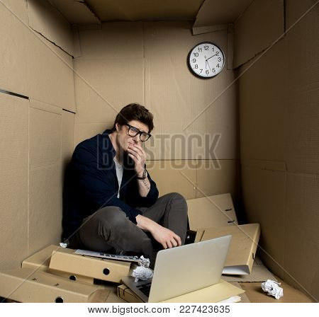 Deep Depression Concept. Full Length Of Young Businessman Is Sitting With Laptop Inside His Small Ca