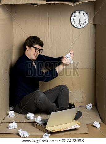 Full Of Fury. Young Businessman Is Sitting On Floor Of His Cramped Carton Office And Shredding Docum
