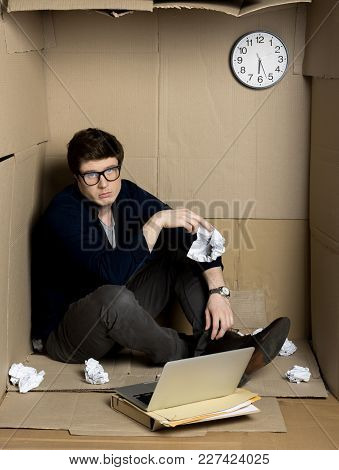 Feeling Hopeless. Full Length Portrait Of Young Businessman Is Sitting On Floor Of His Cramped Cardb