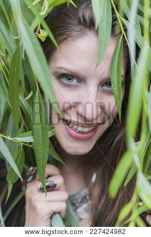 Cheerful Young Beautiful Woman Smiling Through Vibrant Green Willow Branches, Enjoying Nature And Su