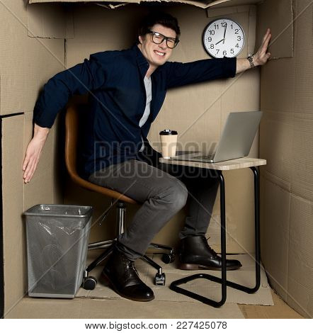 Overcrowding Concept. Full Length Portrait Of Angry Young Employee Is Sitting In Confined Carton Off
