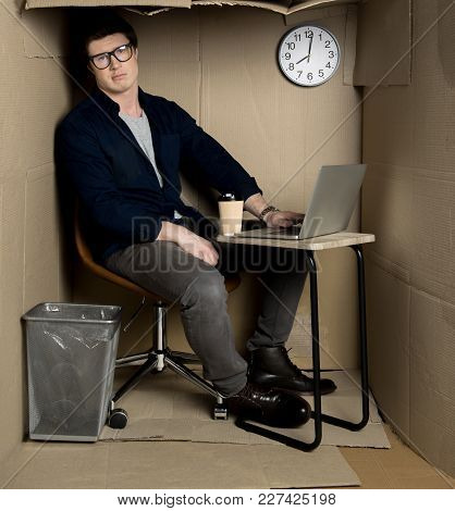 Overwork Concept. Full Length Portrait Of Young Employee Is Expressing Frustration While Sitting At