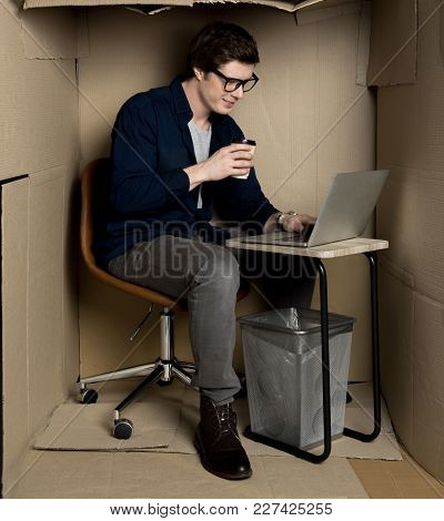 Full Length Of Optimistic Young Manager Is Sitting At Table In Cramped Cardboard Office While Drinki