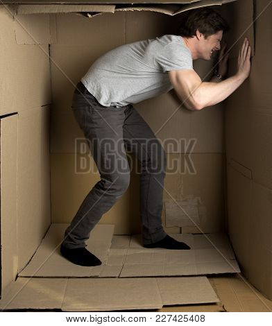 Give Me More Space Concept. Full Length Of Young Man Is Standing In Cardboard Box And Pushing Wall W