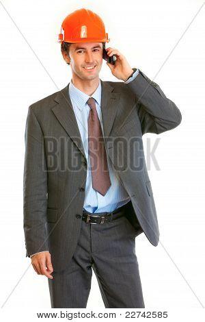 Smiling Businessman In Helmet On Head Talking On Mobile Phone