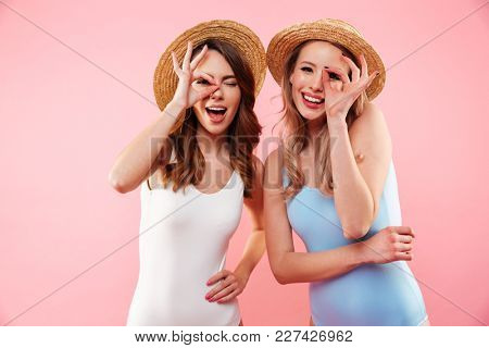 Portrait of two young girls 20s wearing colorful swimsuits and straw hats smiling on camera and looking through fingers isolated over pink background