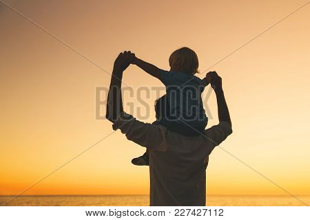 Father And Son Silhouettes At Sunset Sky. Loving Family And Summer Vacation. Man And Kid Boy Playing